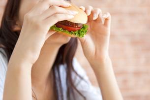 ハンバーガーを食べている女性の写真素材 [FYI01277317]