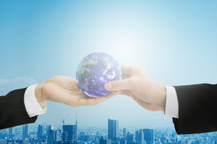 地球を受け渡しするビジネスマンとビジネスウーマンの手の写真素材 [FYI01277661]
