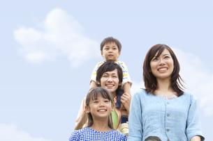 青空のもと笑顔の親子の写真素材 [FYI01278071]