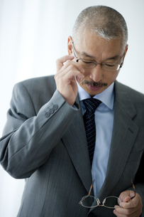メガネをかけ替える中高年ビジネスマンの写真素材 [FYI01278713]
