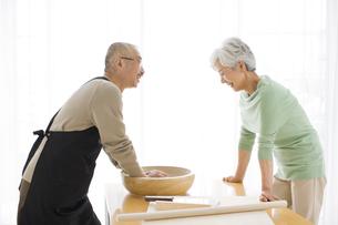 そばを打つ中高年男性と話をする中高年女性の写真素材 [FYI01278758]