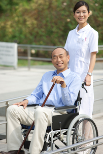 車いすに乗っている男性と看護師の写真素材 [FYI01279093]