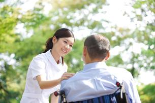 車いすに乗っている男性と看護師の写真素材 [FYI01279102]