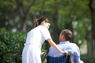 車いすに乗っている男性と看護師の後姿の写真素材 [FYI01279106]