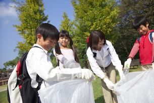 ゴミ拾いをする小学生と先生の写真素材 [FYI01279408]