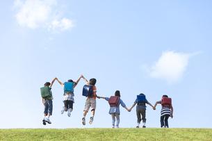 土手で手をつないでジャンプする小学生の写真素材 [FYI01279417]
