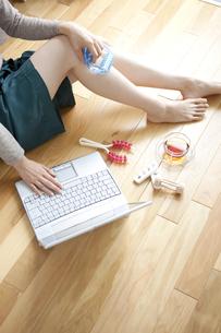 床に座ってパソコンをする女性の写真素材 [FYI01279527]