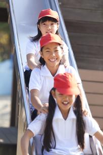滑り台で遊ぶ体操服姿の小学生の写真素材 [FYI01279592]