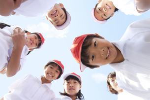 輪になってカメラを覗く体操服姿の小学生と先生の写真素材 [FYI01279594]