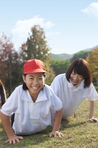 腕立て伏せをする体操服姿の小学生と先生の写真素材 [FYI01279615]