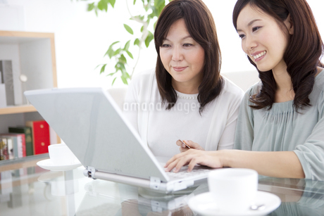 パソコンの画面を見ている母と娘の写真素材 [FYI01279675]