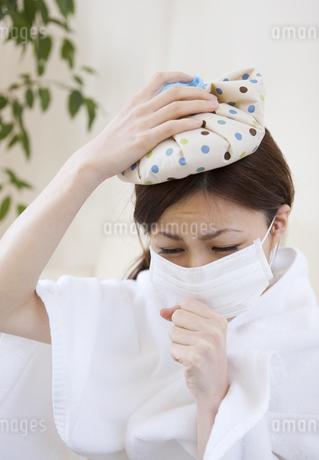 氷のうで頭を冷やして咳き込む女性の写真素材 [FYI01279713]