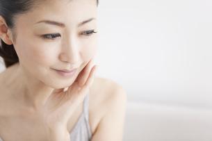 頬に手を当てている女性の写真素材 [FYI01280083]