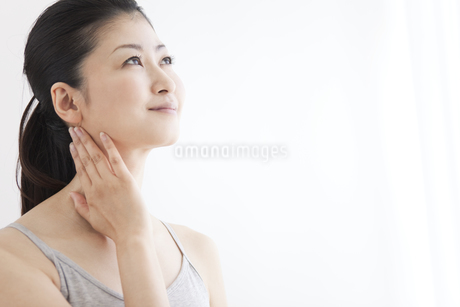 首に手を当てている女性の写真素材 [FYI01280086]