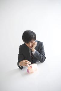 貯金箱にお金を入れようとするビジネスマンの写真素材 [FYI01280229]