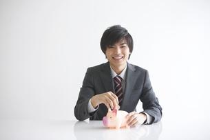 貯金箱にお金を入れようとするビジネスマンの写真素材 [FYI01280234]
