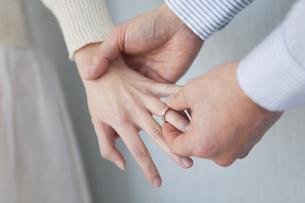 女性の指に指輪をはめる男性の手元の写真素材 [FYI01281006]
