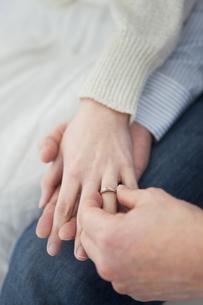 女性の指に指輪をはめる男性の手元の写真素材 [FYI01281007]