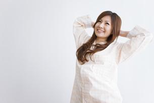 伸びをするパジャマ姿の女性の写真素材 [FYI01281157]