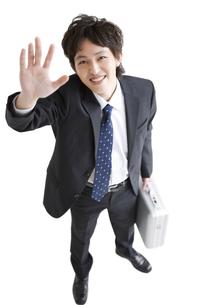 笑顔で手を挙げるビジネスマンの写真素材 [FYI01281424]