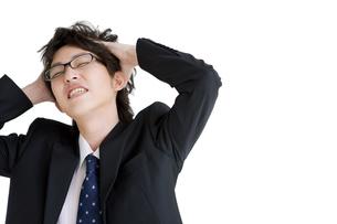 頭を抱えるビジネスマンの写真素材 [FYI01281449]