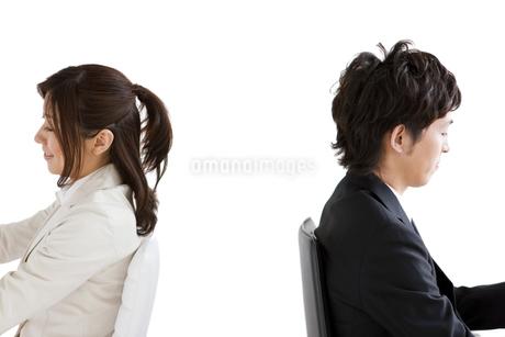 背を向けて座るビジネスマンとビジネスウーマンの写真素材 [FYI01281523]