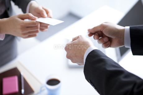 名刺交換するビジネスウーマンとビジネスマンの手元の写真素材 [FYI01281845]