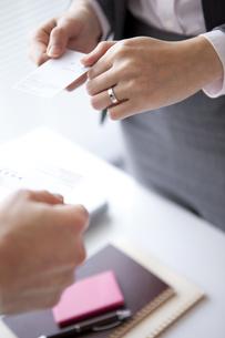 名刺交換するビジネスウーマンとビジネスマンの手元の写真素材 [FYI01281847]