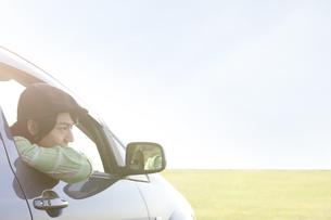 車窓から顔を出す若者男性の写真素材 [FYI01282319]