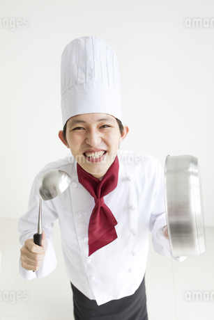 調理器具を持っている笑顔のコックの写真素材 [FYI01282724]