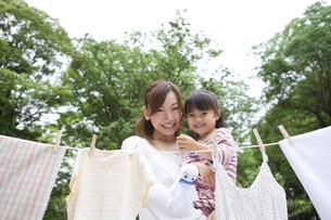 洗濯物を干す親子の写真素材 [FYI01282943]