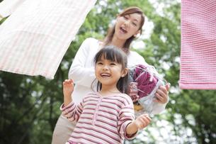 洗濯物を干す親子の写真素材 [FYI01282959]
