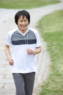 公園で音楽を聴きながらジョギングをする中高年男性の写真素材 [FYI01283071]