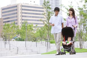 都会の公園でベビーカーを押す両親の写真素材 [FYI01283648]
