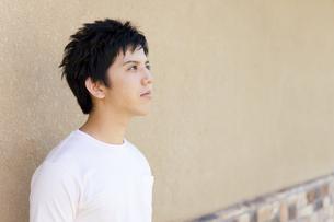 壁の前で考え事をする若者男性の写真素材 [FYI01283773]