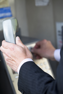公衆電話をかけるビジネスマンの写真素材 [FYI01283835]