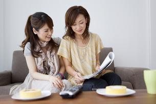 雑誌を見て話す女性2人の写真素材 [FYI01283988]