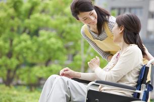 車イスに乗る女性に話しかける介護士の写真素材 [FYI01284032]