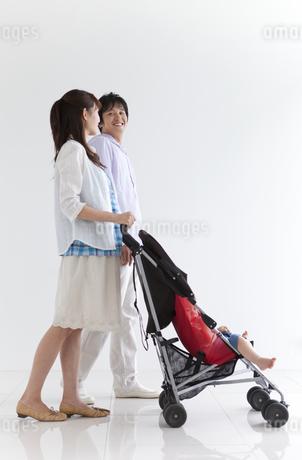ベビーカーを押して歩く夫婦の写真素材 [FYI01284276]