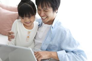 パソコンを見ている笑顔の親子の写真素材 [FYI01284329]