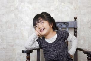 イスのアームにほおづえをつく女の子の写真素材 [FYI01284365]