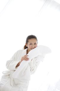 タオルで顔を拭いているバスローブ姿の女性の写真素材 [FYI01284483]