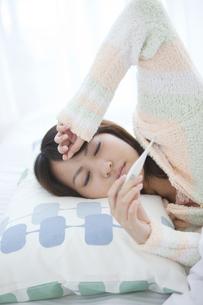 ベッドに横たわって体温計を見ている女性の写真素材 [FYI01284505]