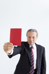 レッドカードを持った中高年ビジネスマンの写真素材 [FYI01284510]