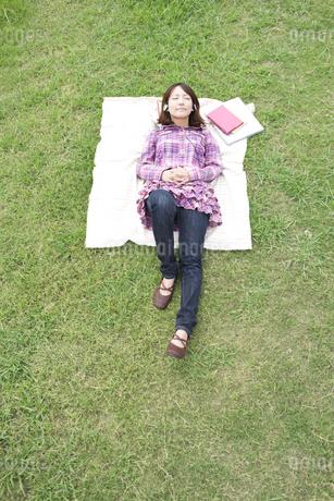 芝生に寝転んで音楽を聴いている大学生の写真素材 [FYI01284534]