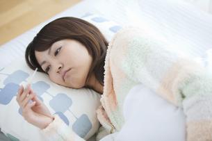 ベッドに横たわって体温計を見ている女性の写真素材 [FYI01284539]