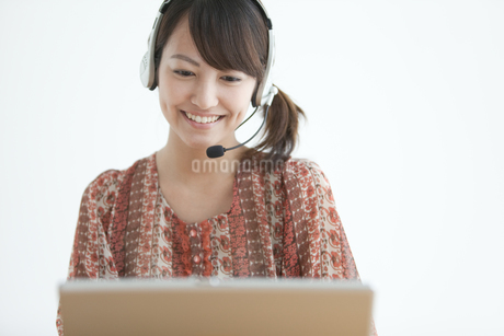 インカムをつけてパソコンを見ている女性の写真素材 [FYI01284703]