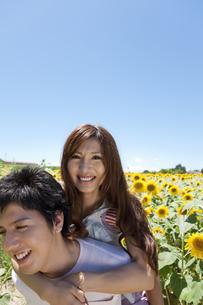 女性をおんぶする男性とヒマワリ畑の写真素材 [FYI01284743]