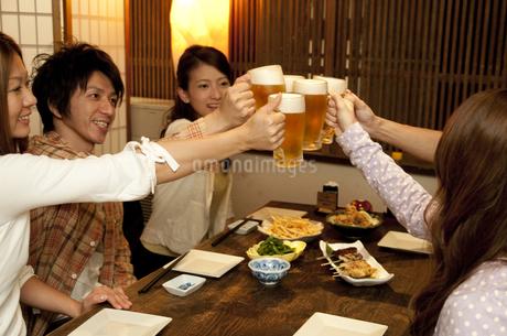 居酒屋で乾杯する若者グループの写真素材 [FYI01284887]