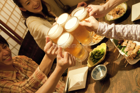居酒屋で乾杯する若者グループの写真素材 [FYI01284891]